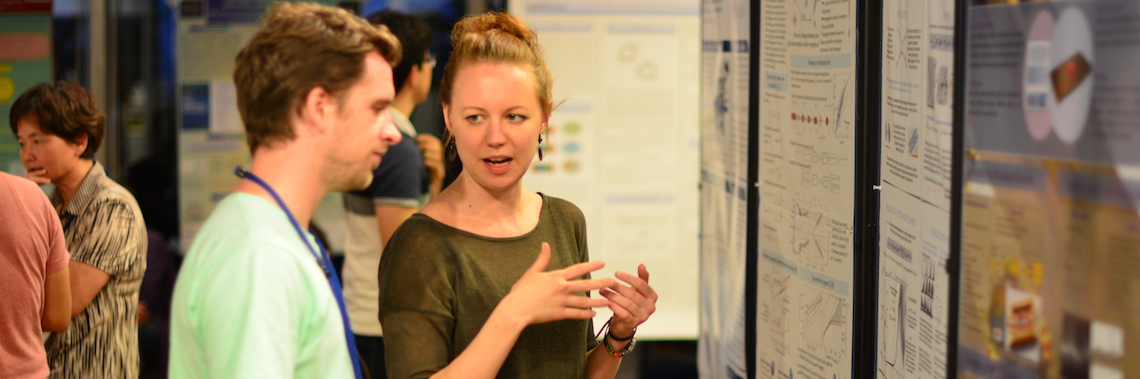 Female researcher explaining her work to a male attendee.