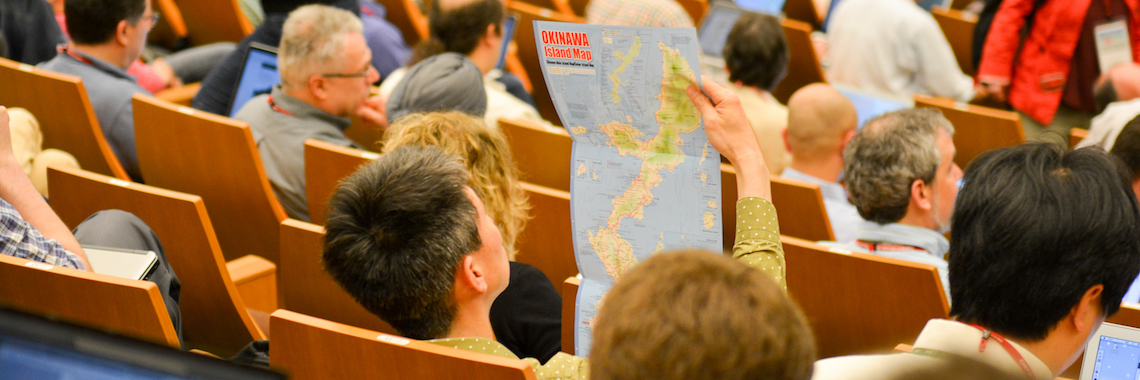 A man looks at a map of Okinawa while waiting for a workshop event to begin.