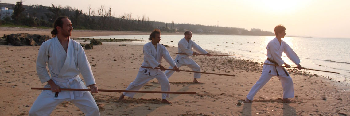 OIST members practicing karate on the beach with the sun behind them