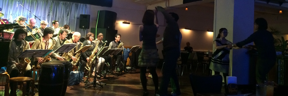 OIST members swing dancing to a full brass band
