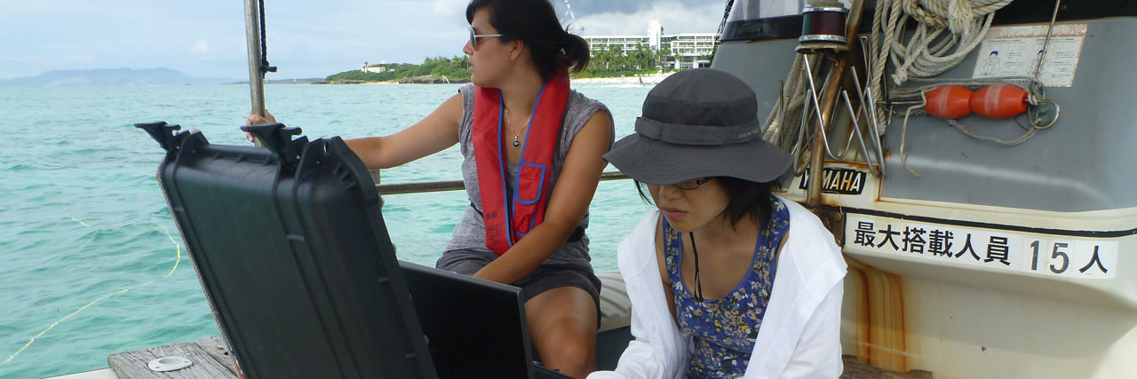 Researcher and faculty on boat doing marine biophysics