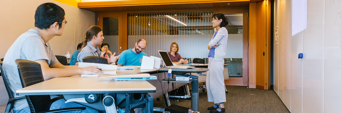 A Japanese woman teaching Japanese as a foreign language to graduate students and researchers.